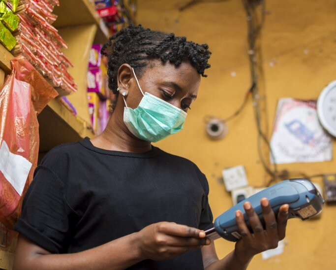 African woman with a face mask using a POS/credit card terminal in a shop