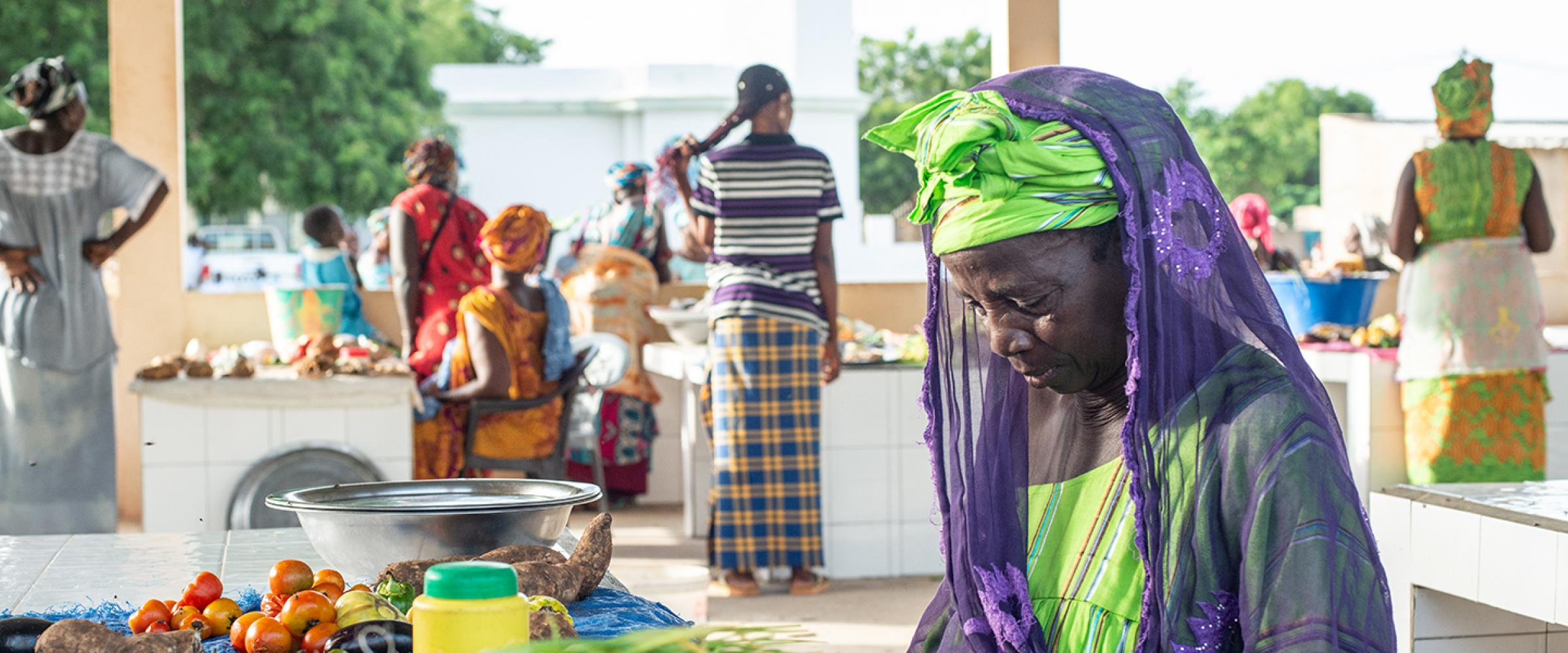 Local produce sold at the market includes items such as: legumes, root vegetables, tomatoes, garlic and onions. Here, Mme Maty Mbaye waits for a client while she cuts green onions.