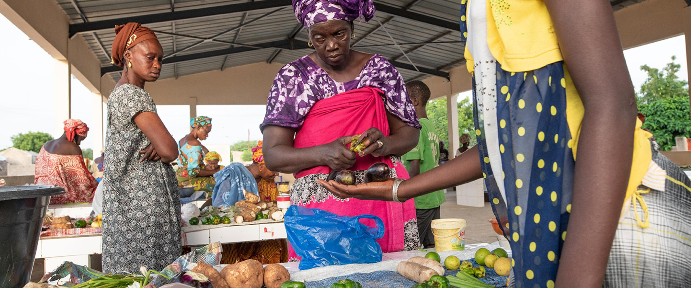Mme Astou Gueye sells product at her stall with two clients
